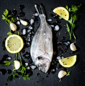 Fresh fish orata over a black stone with vegetables