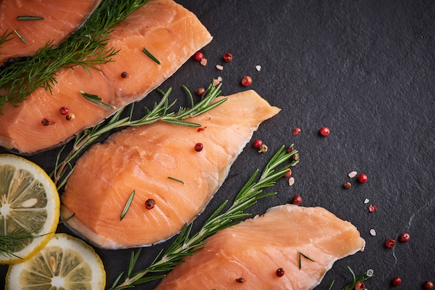 新鮮な魚。生鮭の切り身、黒い石の表面のスパイス、おいしい魚の肉。上面図。健康食品。