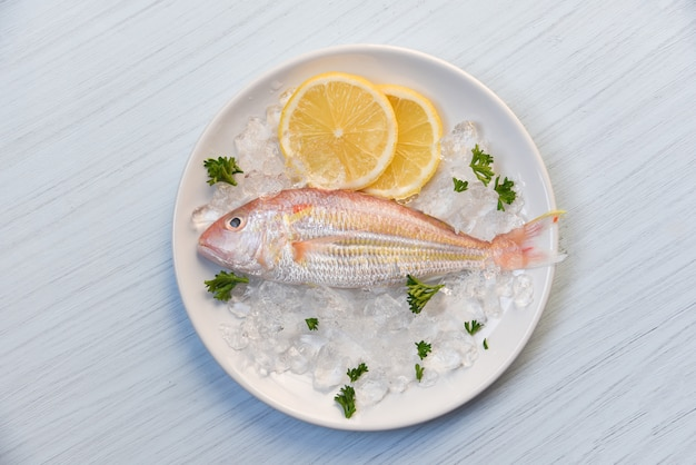 Fresh fish on plate ice with lemon and parsley  top view
