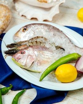 Fresh fish and prawns in ice garnished with pepper, lemon and onion