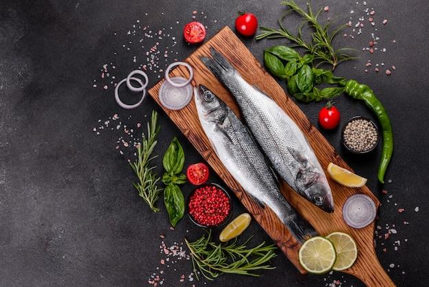 Сибас свежая рыба и ингредиенты для приготовления. сырой морской окунь со специями и зеленью на темном столе