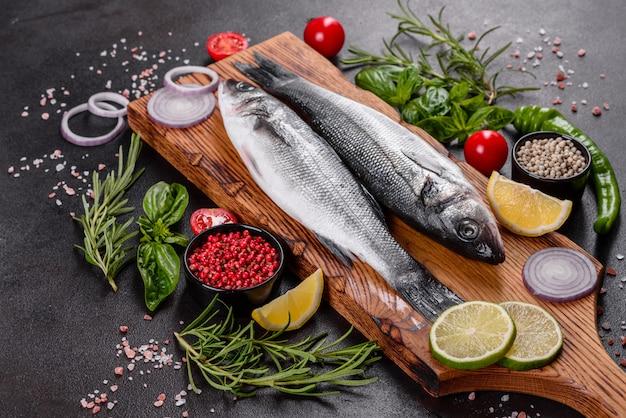신선한 생선 농어와 요리 재료. 어두운 테이블에 향신료와 허브와 생선 농어