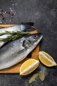 Fresh fish seabass and ingredients for cooking, lemon and rosemary. dark background top view.