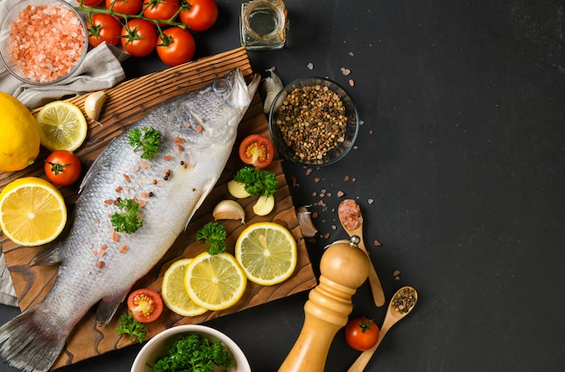 Fresh fish seabass and ingredients for cooking.