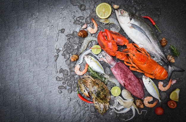 Fresh fish and seafood with ice on black slate