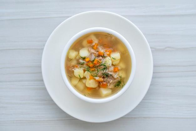 당근, 감자, 양파를 하얀 접시에 넣은 신선한 생선 수프를 닫습니다. 맛있는 저녁 식사는 참치와 생선 스프로 구성되어 있습니다. 평면도
