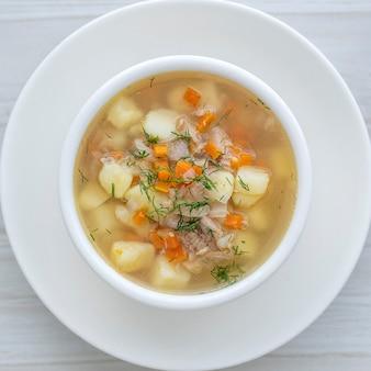 Свежий рыбный суп с морковью, картофелем и луком в белой тарелке, крупным планом. вкусный ужин - ухи с тунцом. вид сверху