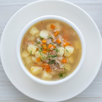 Fresh fish soup with carrots, potatoes and onions in a white plate, close up. tasty dinner consists of a fish soup with tuna. top view