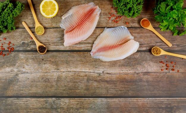 レモンと調味料の木製テーブルに新鮮な魚のティラピア。