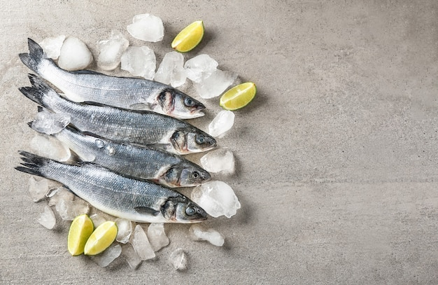 Fresh fish with ice on grey table