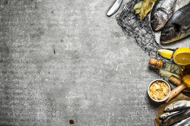 Свежая рыба с лимоном и специями на рыболовной сети на каменном фоне
