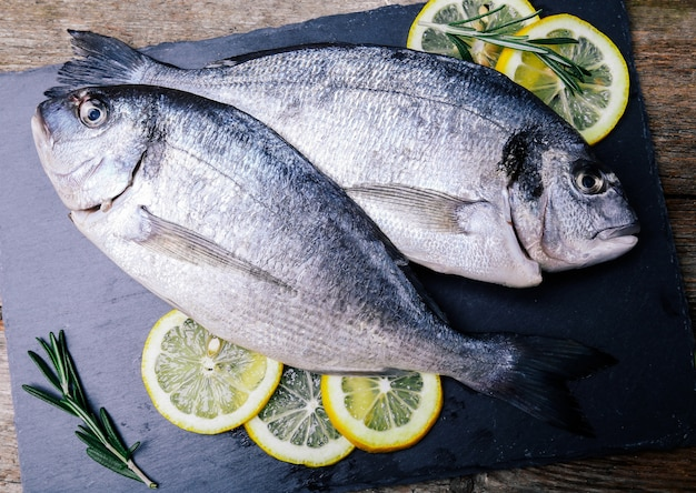 Fresh fish with lemon on rustic board