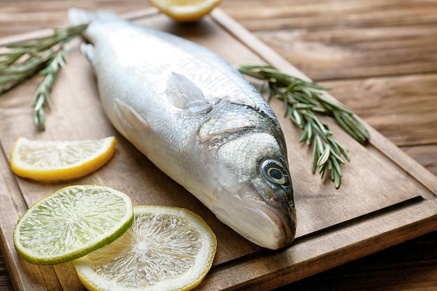 로즈마리와 레몬 나무 보드에 신선한 생선