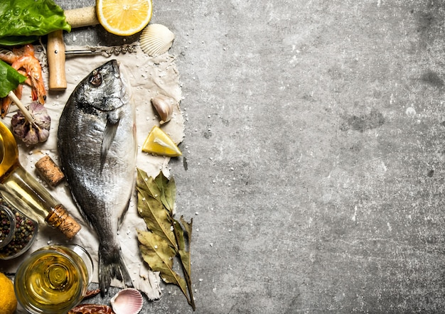 Fresh fish with spices and herbs on a stone background