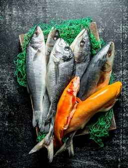 Fresh fish on a wooden tray with a fishing net. on dark rustic background