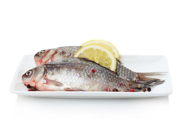 Свежая рыба с лимоном и перцем на тарелке, изолированной на белом
