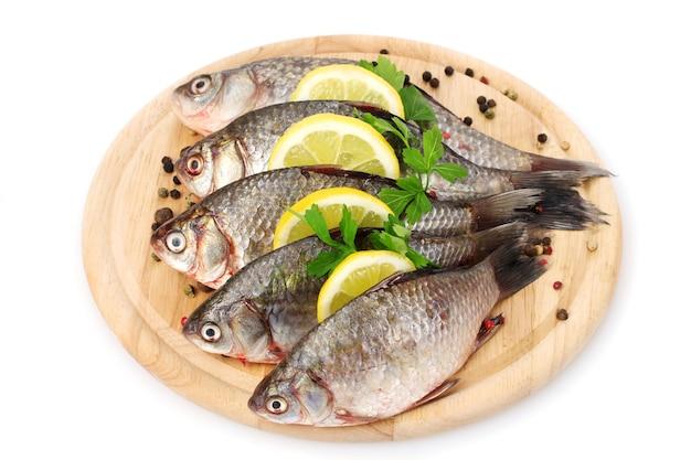 Свежая рыба с лимоном, петрушкой и специями на деревянной разделочной доске, изолированной на белом
