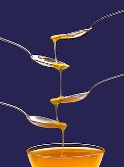 신선한 꽃 꿀이 숟가락에서 파란색 배경의 숟가락으로 떨어집니다. 유기농 비타민 식품.