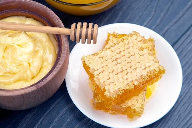 나무 배경에 숟가락이 달린 신선한 꽃 꿀과 벌집. 유기농 비타민 건강식품