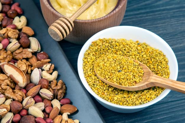 나무 배경에 숟가락이 달린 신선한 꽃 꿀, 견과류, 꽃가루. 유기농 비타민 건강식품