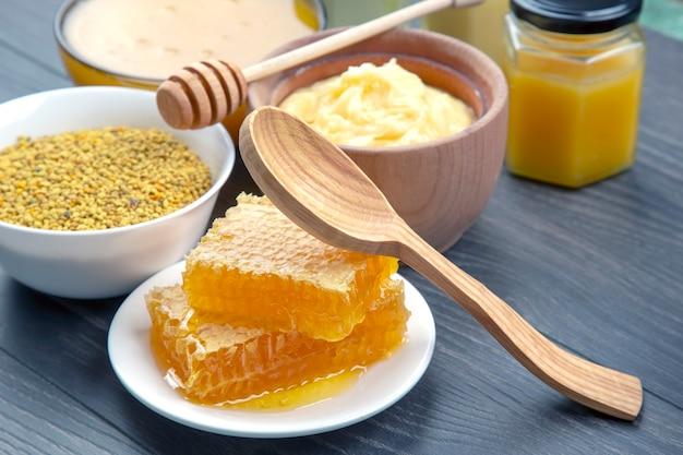 さまざまな種類の生花蜂蜜、花粉、木製の背景にスプーンでハニカム。有機ビタミン健康食品