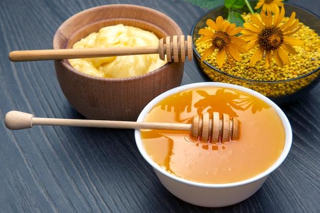 나무 배경에 숟가락이 달린 다양한 종류의 신선한 꽃 꿀, 꽃가루, 벌집. 유기농 비타민 건강식품