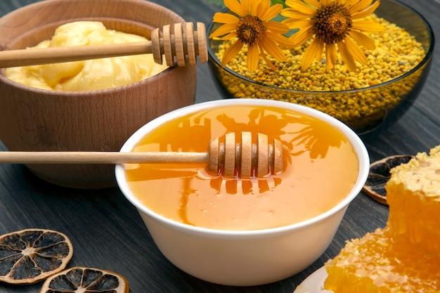 나무 배경에 숟가락이 달린 신선한 꽃 꿀, 꽃가루, 벌집. 유기농 비타민 건강식품