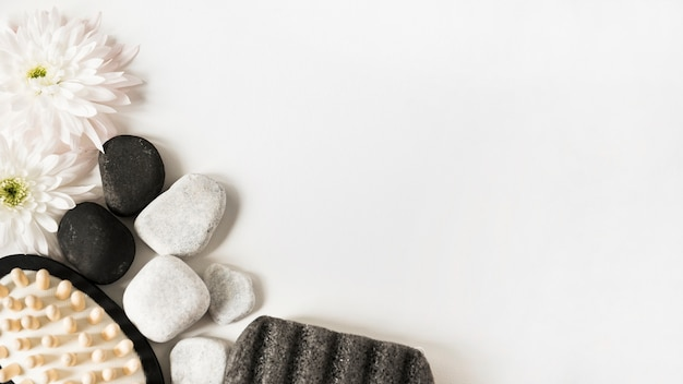 Fresh flower; pebbles; pumice stone and massage brush on white background with space for text