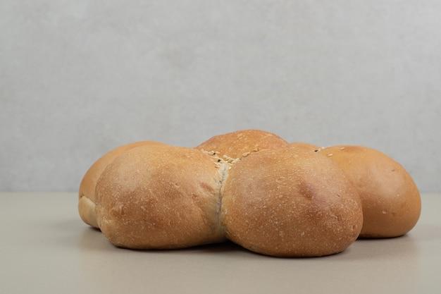 ベージュの背景に新鮮な花の形をしたパン。高品質の写真