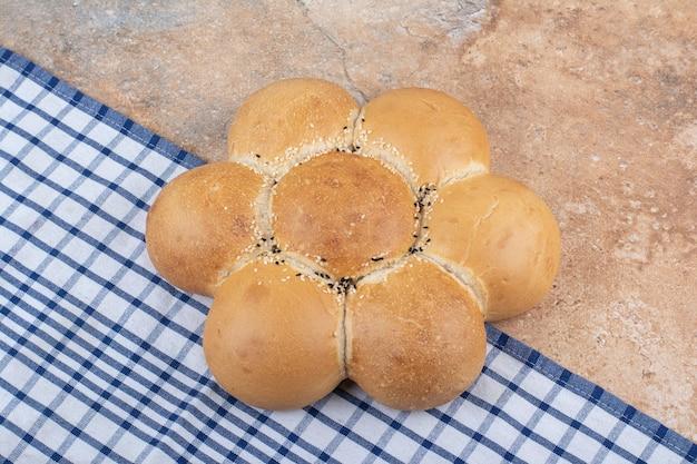 Свежий хлеб в форме цветка на мраморном фоне