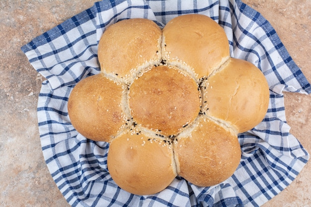 Свежий хлеб в форме цветка на полосатой скатерти
