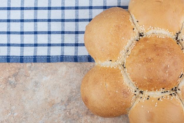 Pane a forma di fiore fresco sulla tovaglia a righe