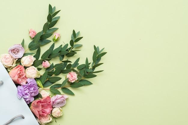 신선한 꽃과 단풍 배달. 녹색 배경에 공간을 복사합니다. 평평하다.