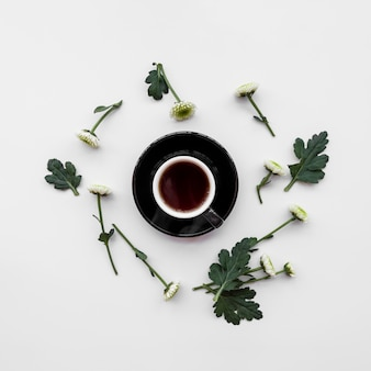 Fresh flowers around cup of coffee