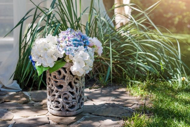 Fresh flowers arrangement in vase in the garden. decorative bouquet for festive event.