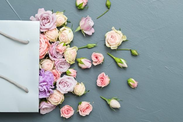신선한 꽃 배달. 회색 바탕에 가방에 모듬 된 장미입니다. 평평하다.