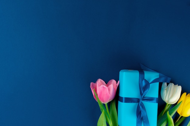 Fresh flowers and gift box with ribbon on classic blue background