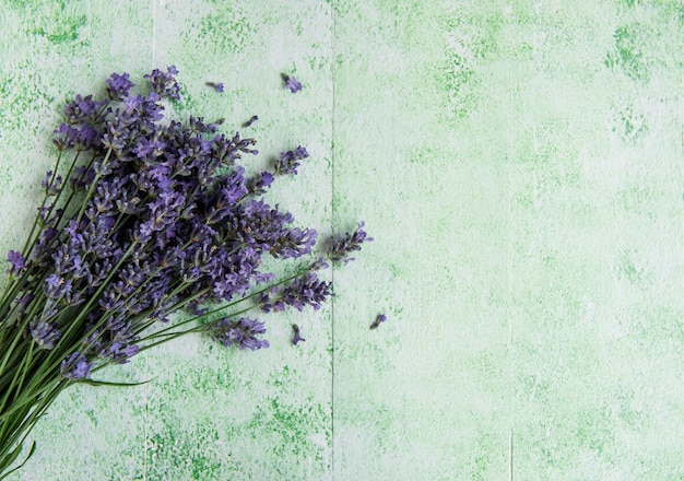 Fresh flowers of lavender bouquet, top view on green wooden background