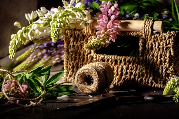 Fresh flowers, leaves, and tools to create a bouquet on a table, florist's workplace