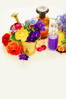 Fresh flowers, mortar and bottles of potions, herbal medicine concept