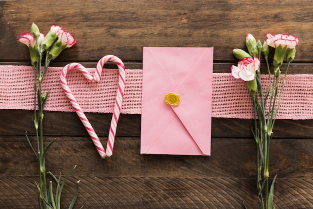 Fresh flowers near ribbon, envelope and candy canes