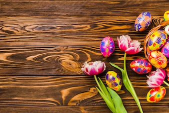 Fresh flowers near set of Easter eggs