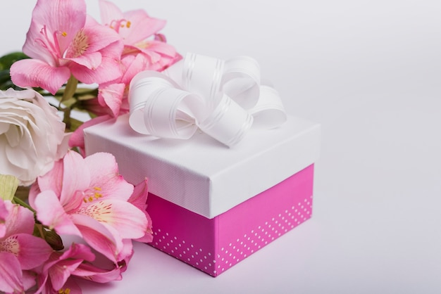 Fresh flowers and present box on white background