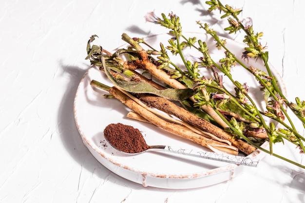 セラミックスタンドに生花、根、チコリの粉。カフェインフリードリンクの天然成分。白い漆喰の背景、クローズアップ
