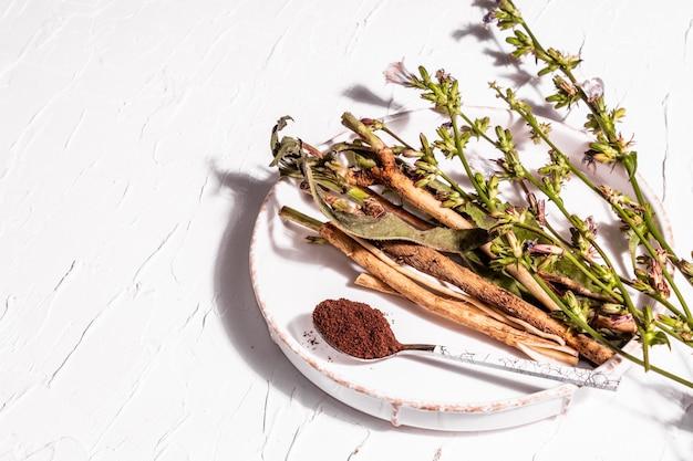 セラミックスタンドに生花、根、チコリの粉。カフェインフリードリンクの天然成分。白い漆喰の背景、コピースペース