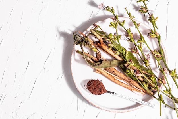 セラミックスタンドに生花、根、チコリの粉。カフェインフリードリンクの天然成分。白い漆喰の背景、上面図
