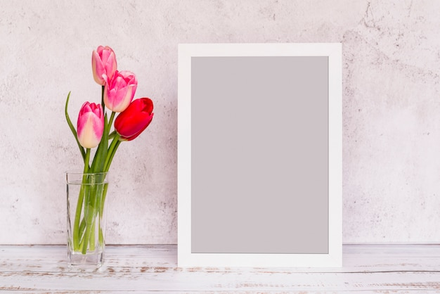 Fresh flowers in vase and frame