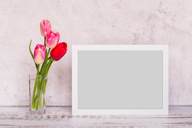 Fresh flowers in vase near frame