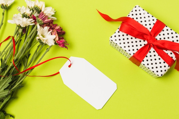 Fresh flowers with white tag and decorative gift box on green surface