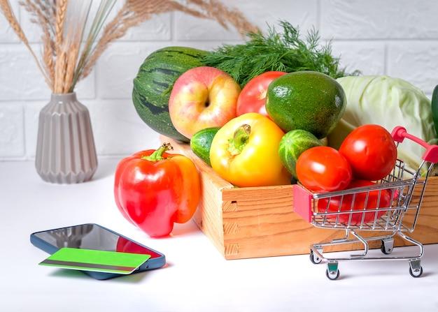 モバイルスマートフォン、オンライン食料品の概念の緑のショッピングカートに生鮮食品と野菜